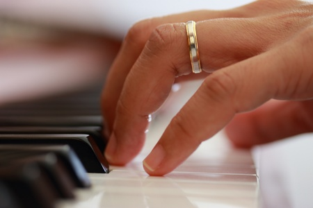Woman hands playing upright piano  Close up view from left  photo