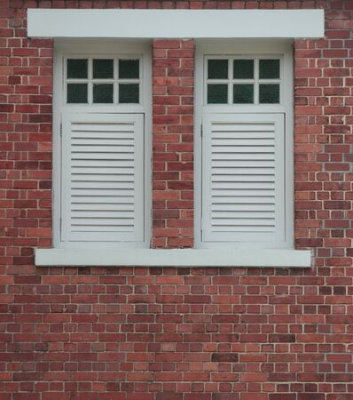 Two closed windows on wall made of red bricks Stock Photo - 14512374