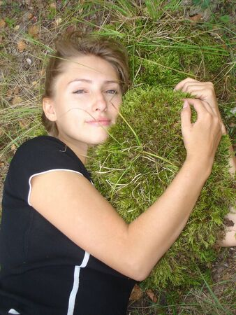 girl lays embraces a moss
