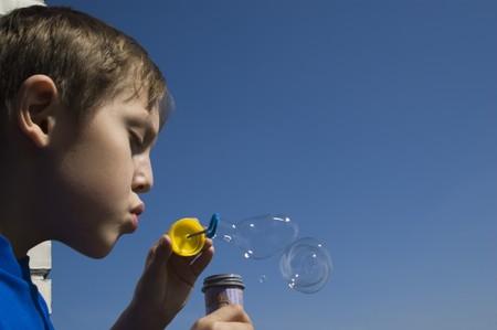 sud: boy blowing soap bubbles