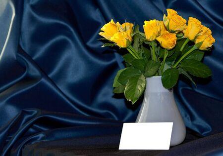 giallo rose con un biglietto in bianco Archivio Fotografico
