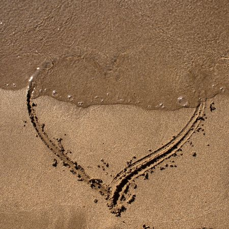 A perfect Valentine love symbol. A heart shape on the sand in a sunny day.