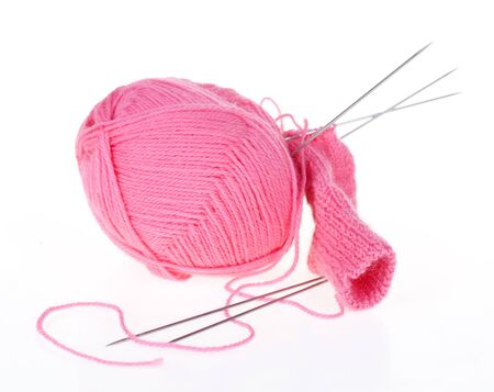 ball of pink thread and knitting spokes
