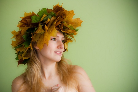Portrait of beautiful girl in wreath of leaves on green background Stock Photo