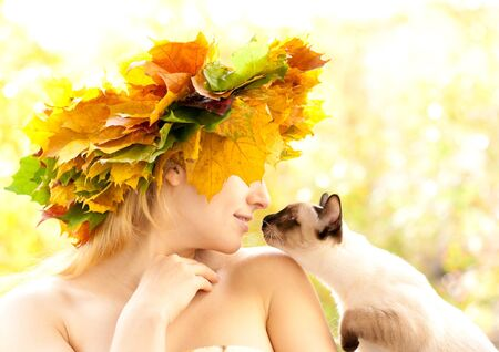 Portrait of beautiful girl in wreath of leaves with a cat photo