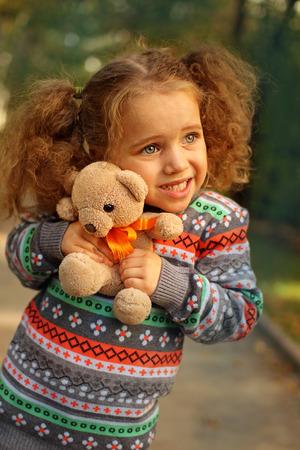 Girl in park hugging a teddy bear