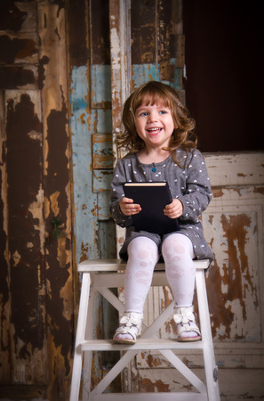Girl sitting on a chair with a book and laughing photo