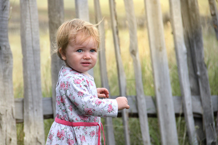 baby toddler standing at the fence Stock Photo
