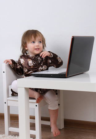Pretty baby looking at laptop