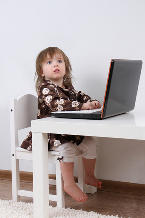 Close-up of pretty baby working at laptop
