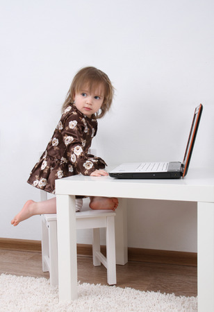 Close-up of pretty baby with a laptop