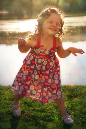 Baby girl dabbles on the lake