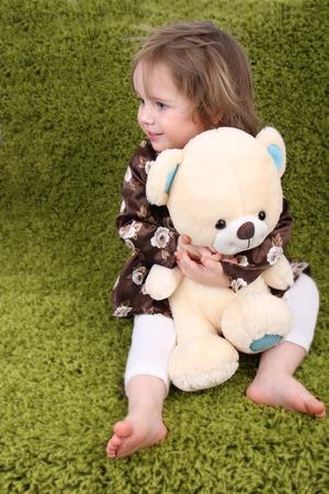 Little baby girl holding a white teddy bear
