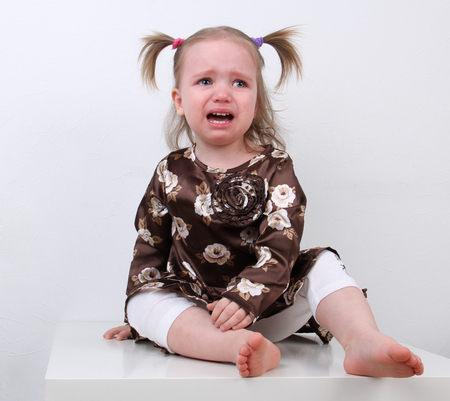 Baby girl crying sitting on a table on a white background Stock Photo