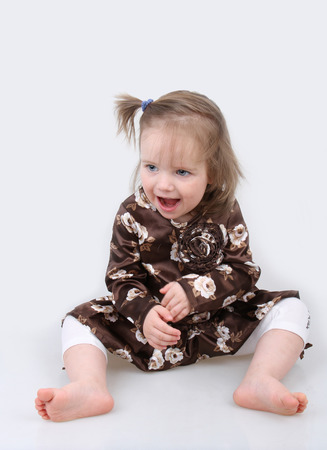 Baby girl sitting on a gray background