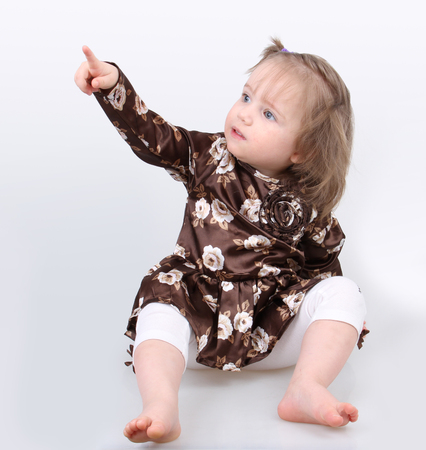 Bambina seduta su uno sfondo grigio presenta con un dito verso l'alto