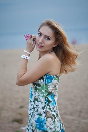 Giovane donna sulla baia con un fiore