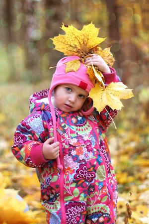 Little baby girl in autumn maple leaves