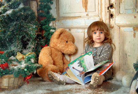 Girl with a book in the Christmas decorations