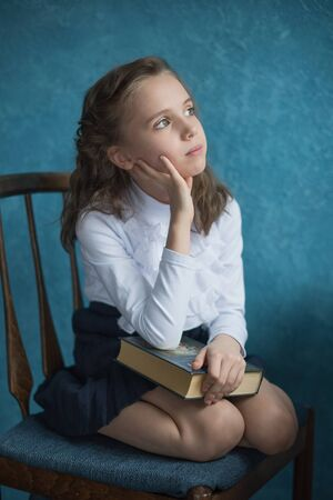 girl holding a book on her lap and thinking