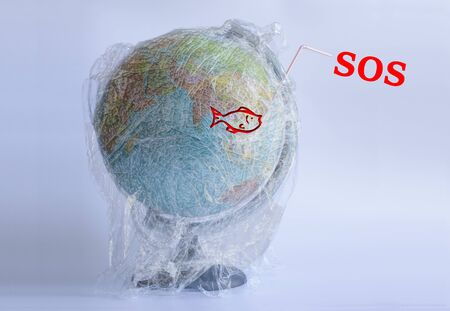 Text SOS and icon of fish on the Model planet Earth in polyethylene plastic disposable package on light grey background. Ecology problems. Concept pollution of environment with polyethylene plastic waste. World Earth Day. Save the planet