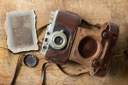 Collage of ancient old vintage film camera with old lether cover on brown old wood backgroundand and sepia photo. Antique, vintage, grunge, classic concept