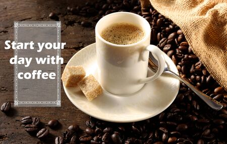 Inspiration life quote Start Your Day with Coffee, cup of coffee on antique wood background with coffee beans. Working from home, home office concept