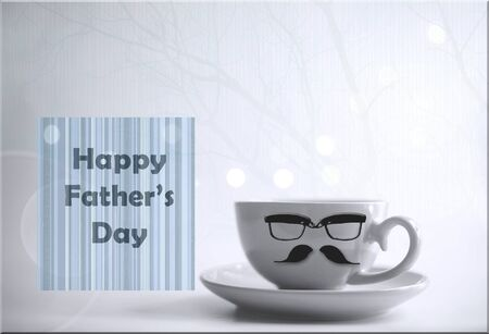 Cup of morning coffee tea with icons of mustache and eyeglasses and greeting card with word Happy Fathers Day on light background with bokeh.