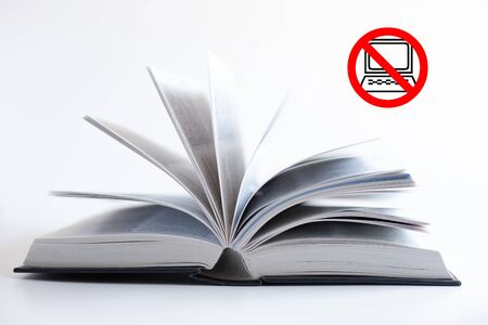 Open book on white background with red icon No Go with icon of computer inside. Self care, time away from technology, finding quiet place with book. Unplug yourself, finding time to calm the brain