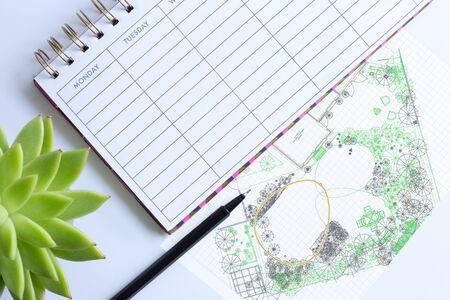 Weekly planner with pen, home plant in soft focus and computer garden design drawing sketch. Landscaping architectural project execution, garden design landscape concept