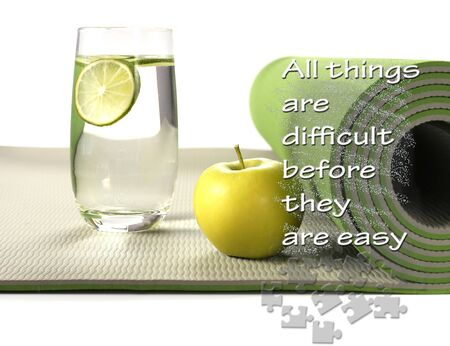 Green yoga mat with apple and glass of water with lemon on white background. Fitness motivation quote All things are difficult before they are easy. Healthy life concept