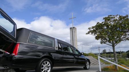 Shot van lijkwagen die een begrafenis arriveert of verlaat