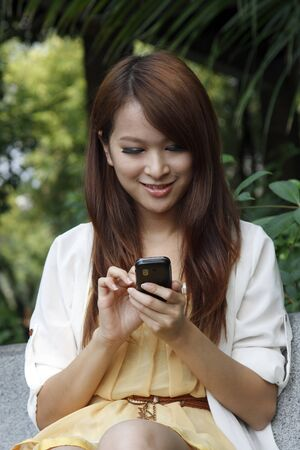 Happy Asian girl using mobile