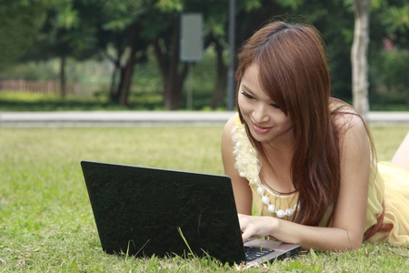 Happy Asia girl using laptop on grass