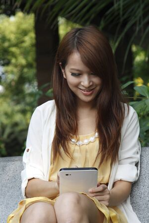 Happy Asia girl holding tablet pc Stock Photo - 13492115