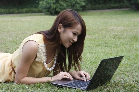Happy Asia girl using laptop on grass Stock Photo - 13492179