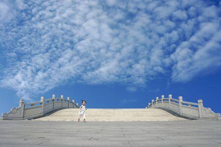 Lovely Asia girl running down stone bridge                  Stock Photo