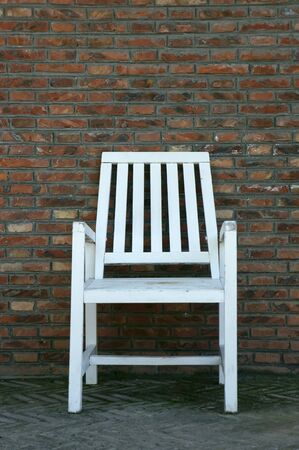 Wooden chair against brick wall