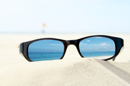 Sunglasses on sandy beach Stock Photo