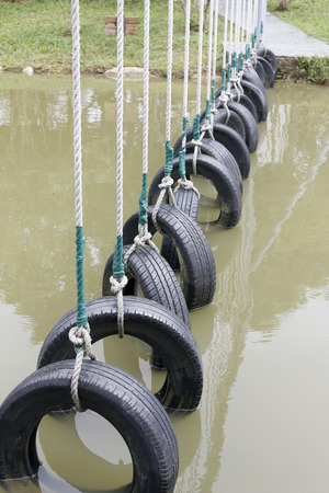Outdoor expansion, Tyres hanged with ropes over water, people can across the water by holding the ropes and step on the tyres