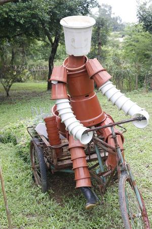 Doll gemaakt door bloempotten het besturen van een driewieler