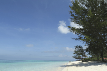 Blauwe zee over blauwe lucht en witte wolken.