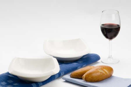 plates, cups dishes with red wine and bread photo