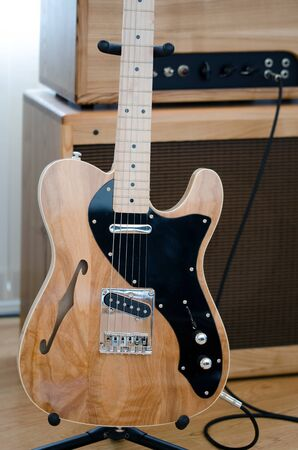 Electric guitar with head amp in background.