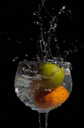 Lemon and orange splashing into a glass of water