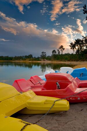 Pedal boats of various colours lined up at lake bank Stock Photo