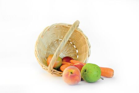 Fruit and vegetables in a basket over white background