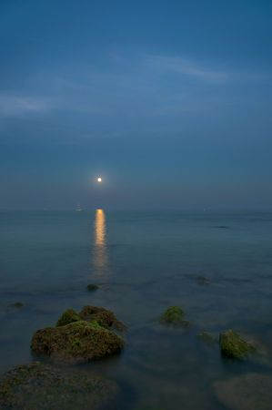 Beautiful image of the moonlight over beach, with a boat gliding in the horizon Stock Photo - 4684842