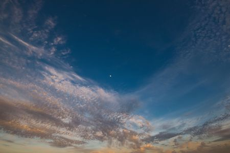 Colorful clouds in a bright blue sky with the moon