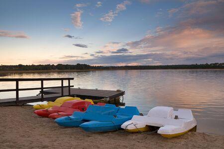 Pedal boats of various colors lined up at lake bank Stock Photo